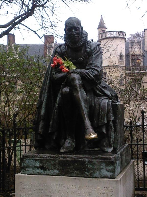 statue de Montaigne en face de la Sorbonne. Son pied a été si touché qu'il luit. Quelqu'un lui a mis un bouquet de tulipes dans les bras