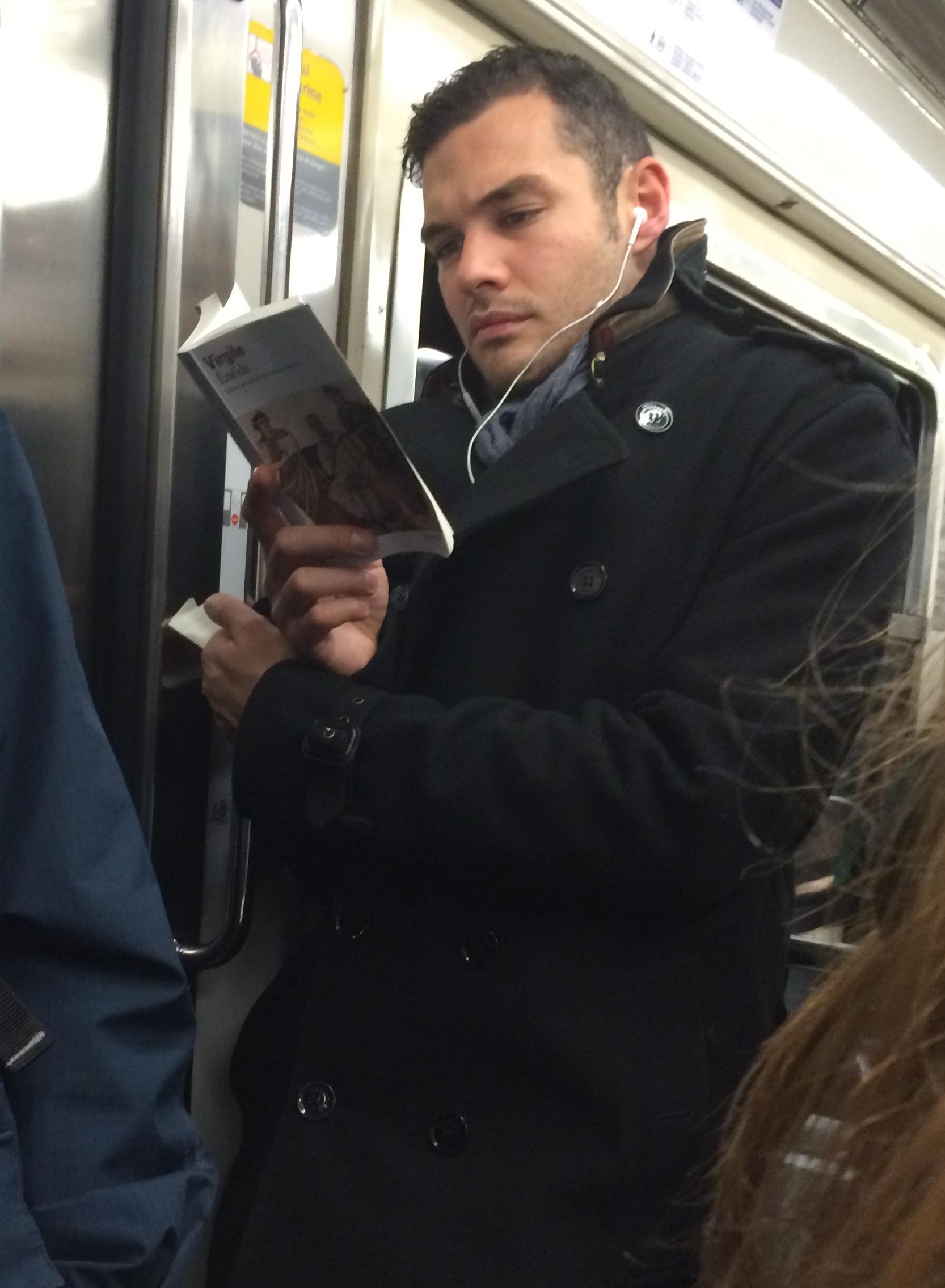 Jeune homme en manteau, debout dans le métro, lisant l'Enéide
